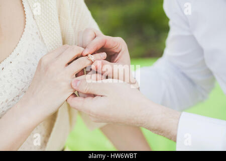 the offer to marry. hands of the man dressing a ring on the belo - Stock Photo