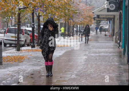 It is snowing and lady (other people too) wearing boots, scarf & winter coat with hood up, walks past shops on The - Stock Photo