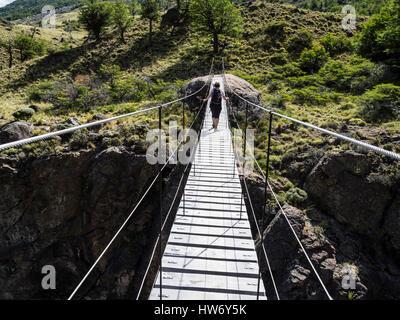 Woman walks over suspension bridge crossing river Rio Aviles, hiking trail 'Aviles loop', Park Patagonia,  Patagonia, - Stock Photo