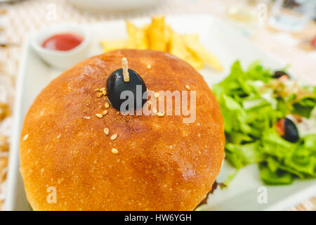 Burger served with salad, chips and tomato ketchup - Stock Photo