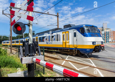 Hoek van Holland, the Netherlands - July 6, 2016: Dutch electric train going through crossing - Stock Photo