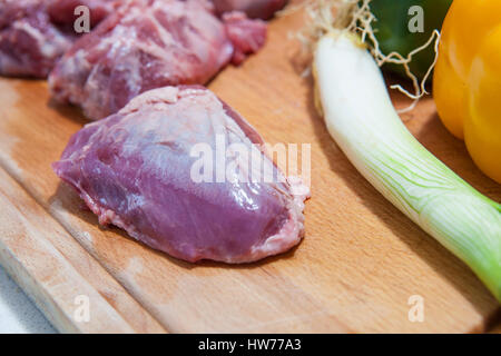 Raw meat cheek pieces of iberian pork with vegetables over wooden board. Isolated over white background - Stock Photo