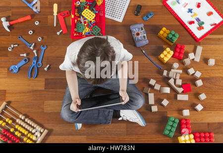Little boy playing with tablet computer. Lot of toys around him on the wooden floor. Top view - Stock Photo