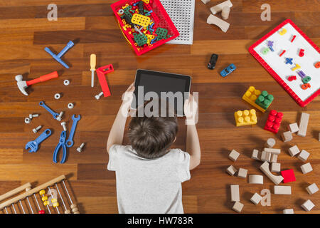 Little kid lying and playing with tablet computer. Lot of toys around him on the wooden floor. Top view - Stock Photo
