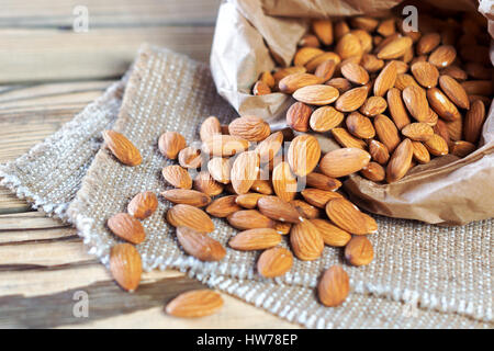 Almonds, pour out on wooden table out of a paper bag. Healthy eating. - Stock Photo