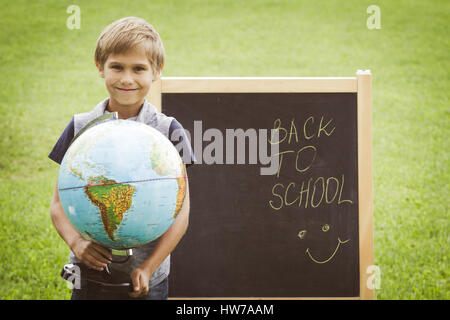 Schoolboy with a globe against the blackboard. Education Back to school concept - Stock Photo