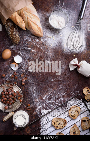 Bakery produce - bread, baguette, cookies over rustic background. Baking ingredients - flour, nuts, eggs, milk. - Stock Photo