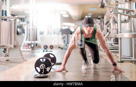 Young determined athletic man in start position in health club - Stock Photo