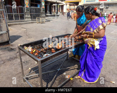 women lit small oil lamps at temple in madurai, india - Stock Photo
