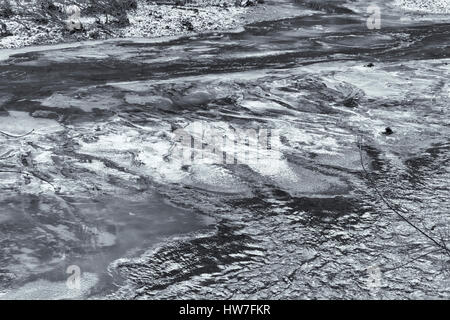 Ice patches on river divert flow - Stock Photo