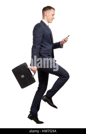 Running businessman with his briefcase and mobile phone on white - Stock Photo