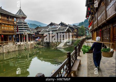 China, Guizhou, Zhaoxing, little capital of the Dong, woman returning form the garden - Stock Photo