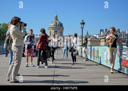 France Paris area listed as World Heritage by UNESCO Footbridge of the arts (or Pont des Arts) groups of tourists - Stock Photo