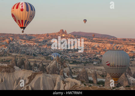 GOREME, TURKEY- SEPTEMBER 29, 2013: Hot air balloons lifting off early morning over Cappadocia. - Stock Photo