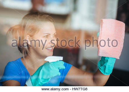 People, housework and housekeeping concept - happy woman in gloves cleaning window with rag and cleanser spray at - Stock Photo