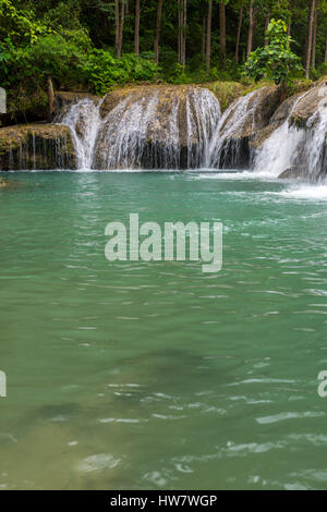 Secret single tier waterfall surrounded by deep rainforest jungle. - Stock Photo