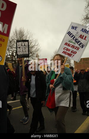 London, UK, 18th March 2017.Two women hold up placards as campaign group Stand Up to Racism holds a march through - Stock Photo