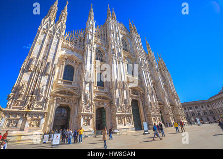 Milan, Italy - March 7, 2017: Tourists walking and taking pictures with pigeons in Piazza Duomo of Milano fashion - Stock Photo