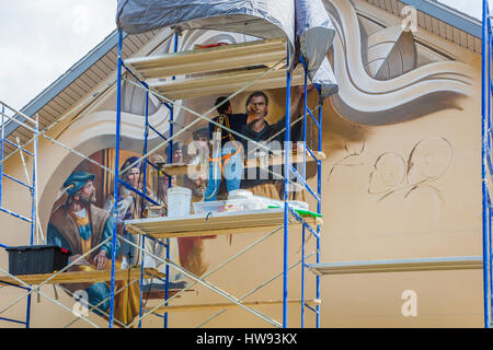 Artist painting mural on church building wall in Lake Placid Florida known as the Town of Murals - Stock Photo