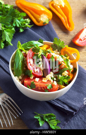 Fresh organic tomato and couscous bulgur salad Tabbouleh with vegetables and greens - healthy vegetarian vegan diet - Stock Photo