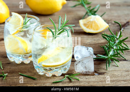 Alcoholic drink (gin tonic cocktail) with lemon, rosemary and ice on rustic wooden table, copy space - Stock Photo