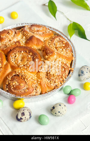 Easter pastry. Fresh Homemade Creamy Cinnamon Buns with Nuts. Cinnamon Rolls with Cream Cheese for Easter Breakfast - Stock Photo