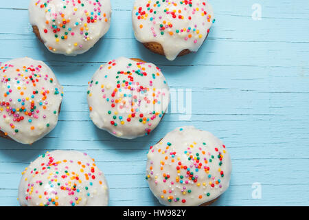 Easter pastry. Fresh Homemade Carrot Mini Cakes with White Creamy Sugar Icing and Colorful Decor over blue wooden - Stock Photo