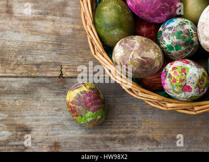 Group of colorful Easter eggs decorated with flowers made by decoupage technique, in a basket on wooden background/ - Stock Photo