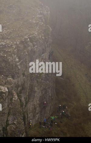 Group of rock climbers in fog at Cheddar Gorge ascend cliff in Somerset, UK, in one of Britain's most impressive - Stock Photo