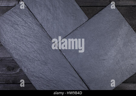 Slate stone board on dark wooden table, top view with copy space - Stock Photo