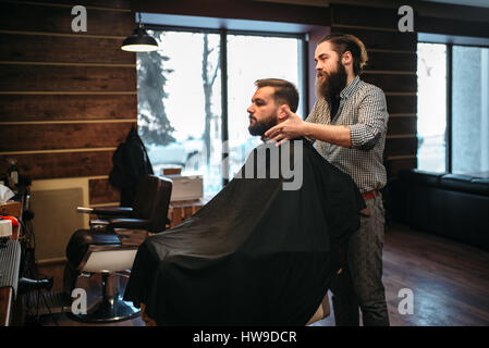 Bearded man in salon cape at the barbershop, barber prepares to ...