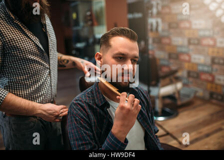 Male client combing his beard at the barbershop, professional barber on background - Stock Photo