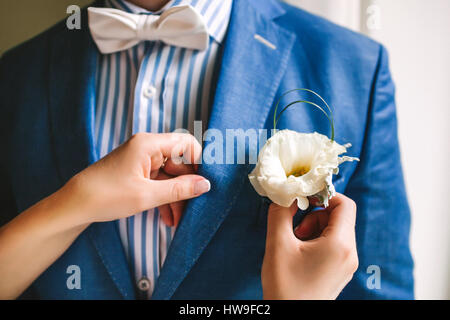 Yellow boutonniere pinned to a grooms jacket - Stock Photo