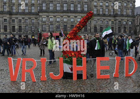 Amsterdam, Netherlands. 18th Mar, 2017. Syrians pose at a number 6 made from flowers and the word 'Freedom'. Syrians - Stock Photo