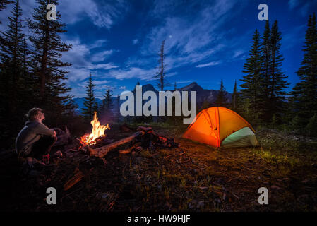 Man looking up at the stars next to campfire and tent at night - Stock Photo