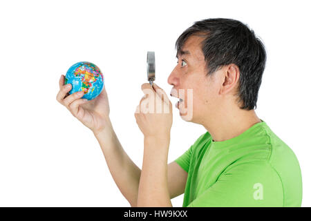 Asian Chinese Man Looking At Globe Through Magnifying Glass in isolated White Background - Stock Photo