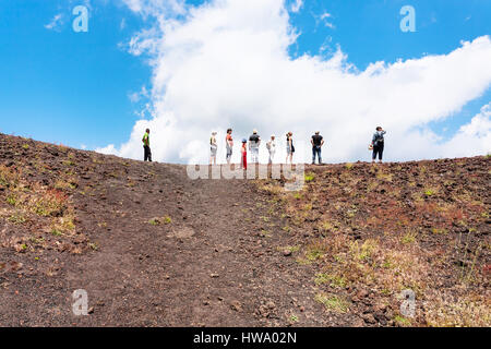ETNA, ITALY - JULY 1, 2011 - tourists on the edge of old crater of Etna volcano. Mount Etna is active volcano on - Stock Photo