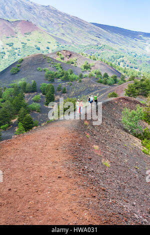 ETNA, ITALY - JULY 1, 2011 - tourists walk on path between old craters of Etna mount. Mount Etna is active volcano - Stock Photo