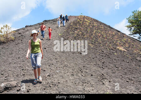 ETNA, ITALY - JULY 1, 2011 - tourists walk on ridge between old crater of Etna mount. Mount Etna is active volcano - Stock Photo