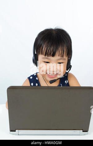 Asian Little Chinese Girl in Headset with Laptop isolated on White Background - Stock Photo
