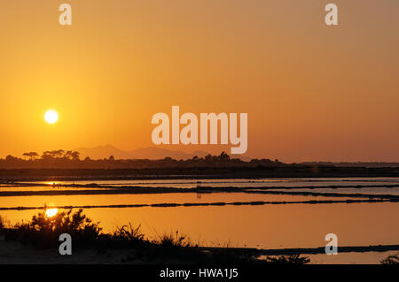 Sunset at the saltpans of Marsala in Sicily - Stock Photo