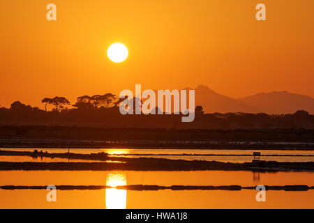 Sunset at the saltpans of Trapani in Sicily - Stock Photo