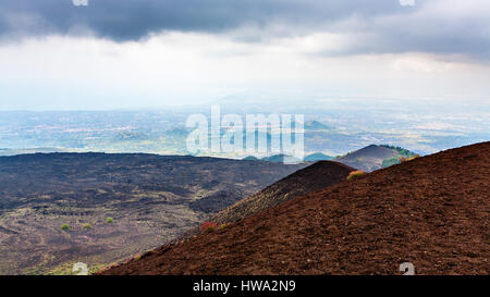 travel to Italy - view of lava fields on Mount Etna and Ionian Sea coast in Sicily in summer day - Stock Photo