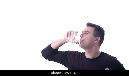 Young man drinking water from a glass cup white background - Stock Photo