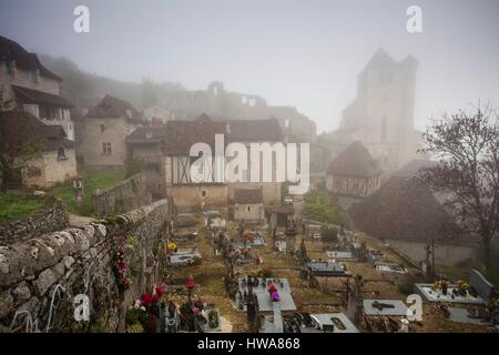 France, Lot, St Cirq Lapopie, town overview in fog with 15th century church - Stock Photo