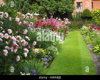Chenies Manor sunken garden, Buckinghamshire in Sept. Dahlia display in full bloom, facing the manor house with - Stock Photo