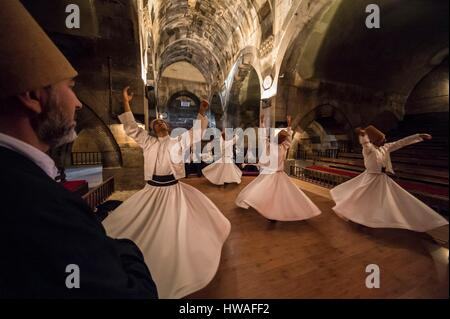 Turkey, Cappadocia, Avanos, whirling dervishes turn looking for mystical ecstasy in Seljuk caravanserai Sarihan - Stock Photo