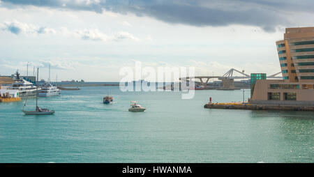 Boats navigating amongst moored counterparts in harbor at Port Vell in Barcelona, Spain.  Ships out on the horizon, - Stock Photo