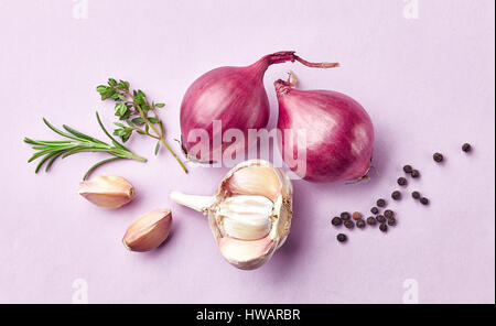 composition of red onions and spices on purple background, top view - Stock Photo