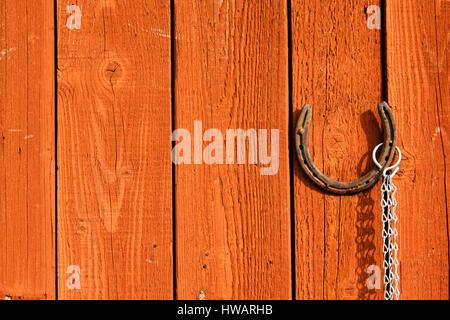 Old rusty horseshoe hanging on a brown wooden door - Stock Photo